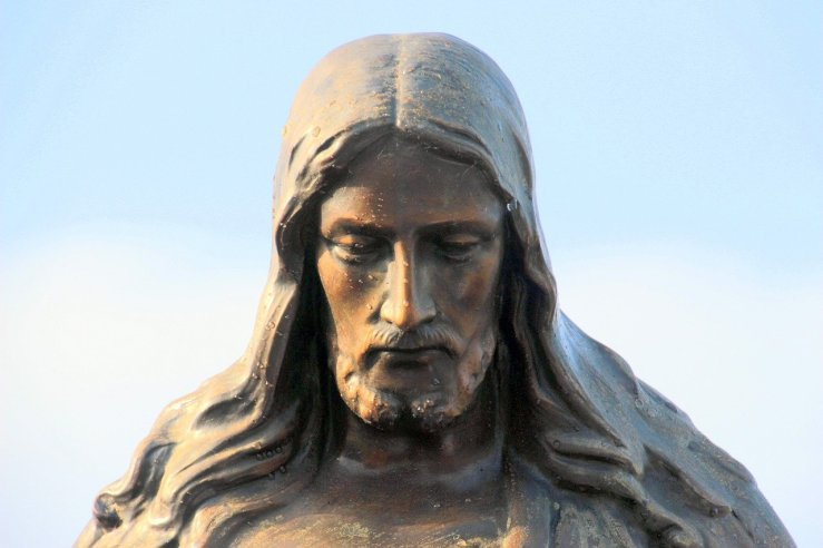 A statue of Jesus with His face looking downward. His mouth is closed and he seems contemplative.
