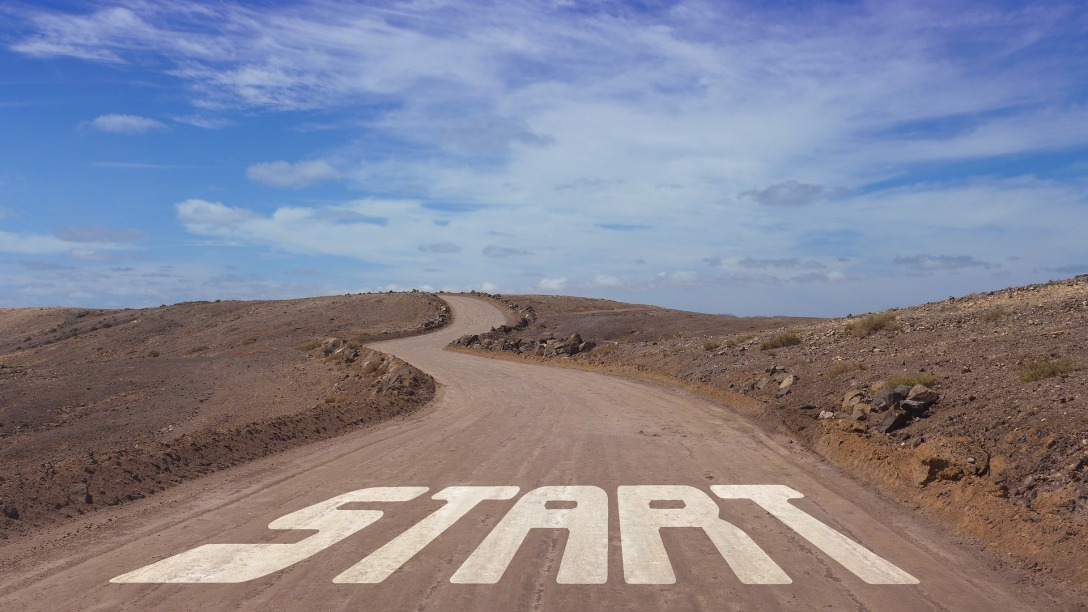 "A dirt road that turns and goes to the horizon. The side of the road is all dirt and there is not a tree anywhere. At the bottom of the image, on the road, is the word ""start."""