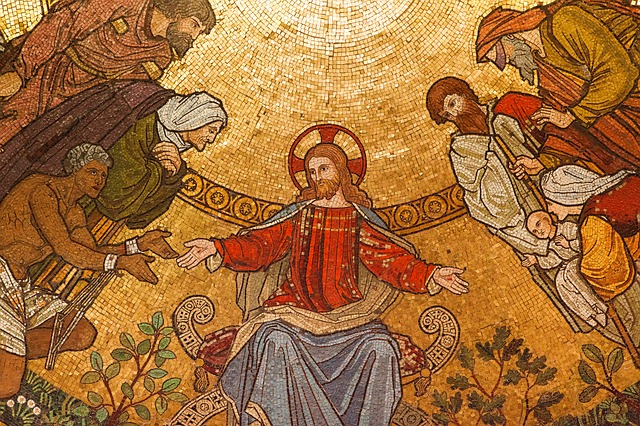 A close up of a mosaic depicting Jesus with His followers. His hands are outstretched and He may be sitting. On either side of Him are all sorts of people. Middle-aged men, a widow, a mother and her child, a slave, and more.