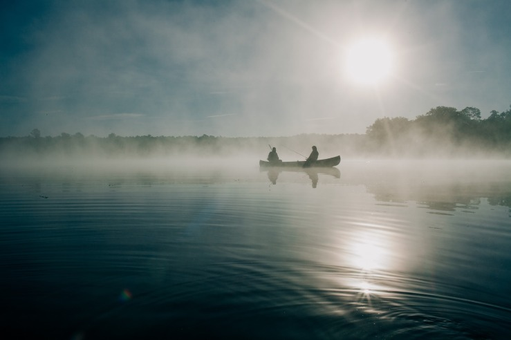 Two people are in a canoe in the early morning. Mist is over the water and trees can be seen on the horizon. Near the top right of the boat is the rising sun. Its reflection is visible on the water.