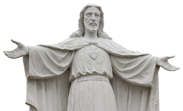 A statue of Jesus with His arms open wide in a welcoming gesture. He looks strong. On His check is what looks like a heart with rings on it. Light is radiating from it a little.