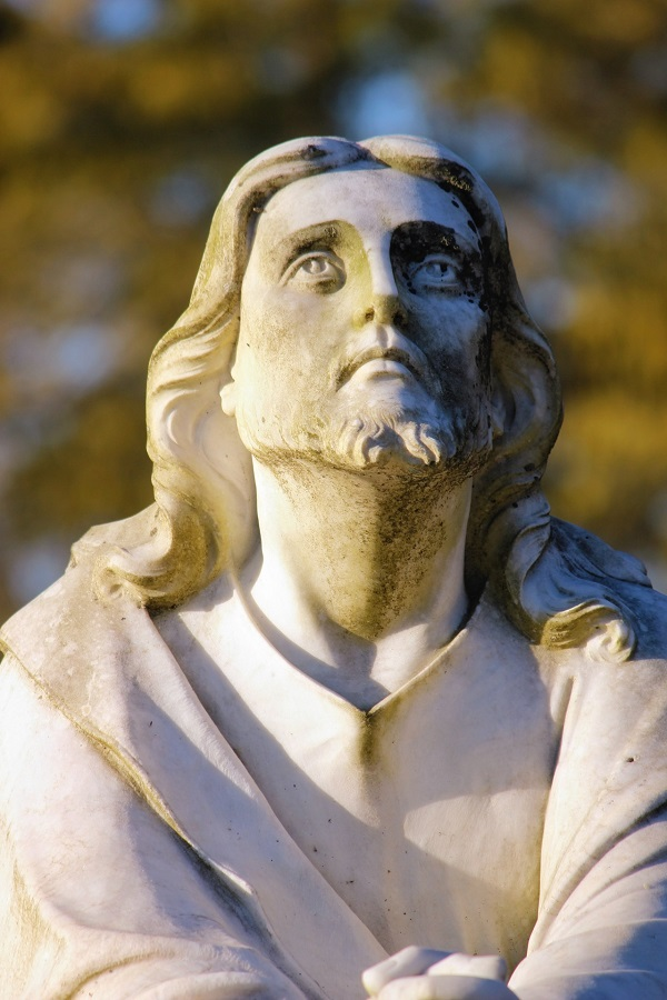 A statue of Jesus looking upward to the heavens and His hands together. He is wearing His typical garb.