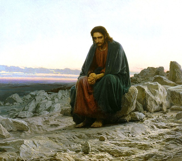 A painting of Jesus in a desolate place. He is sitting on a boulder with his hands together. Rocks are all around Him and there are no trees. He is looking downward like He is deep in thought. This could be Him during His time in the wilderness, or when He left to go pray.