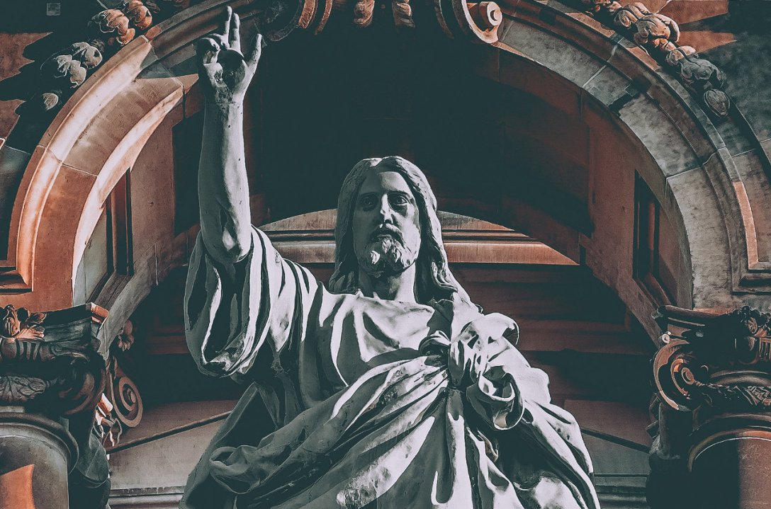 A sculpture of Jesus. His right hand is raised and He is looking ahead. He looks like He is in control. He is wearing a tunic. An arch with columns can be seen behind Him.