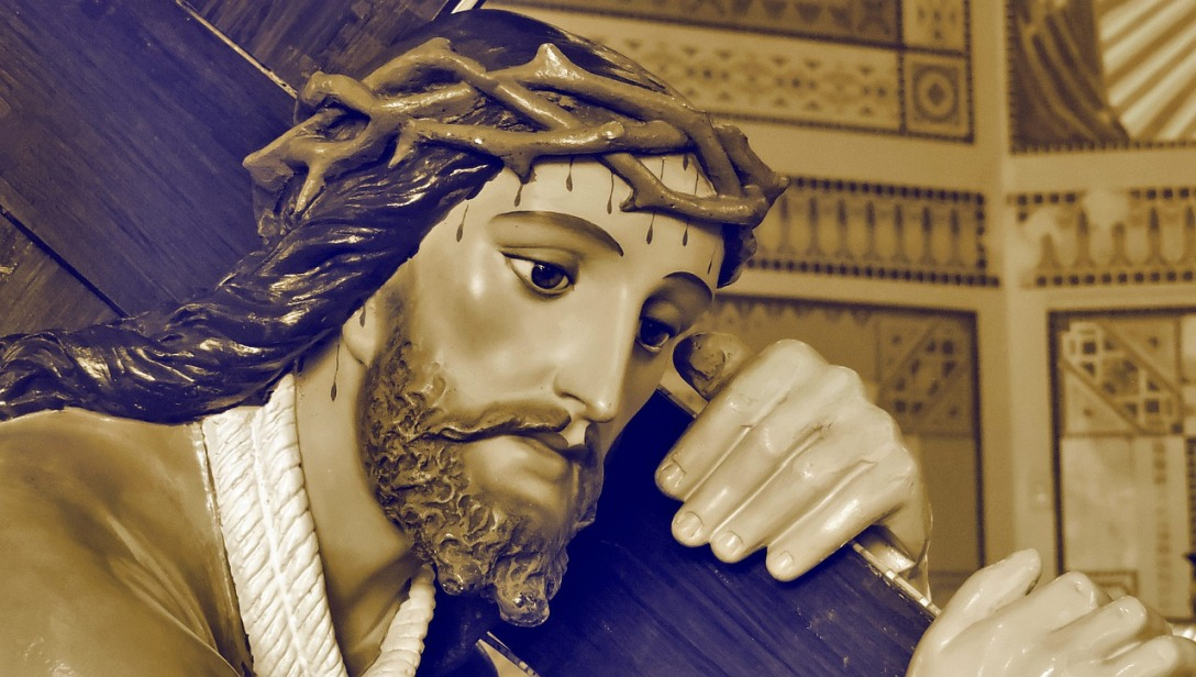A close-up of a statue of Jesus. He is carrying His cross with a crown of thorns on His head. Drops of blood can be seen on His forehead, and other places of His head.