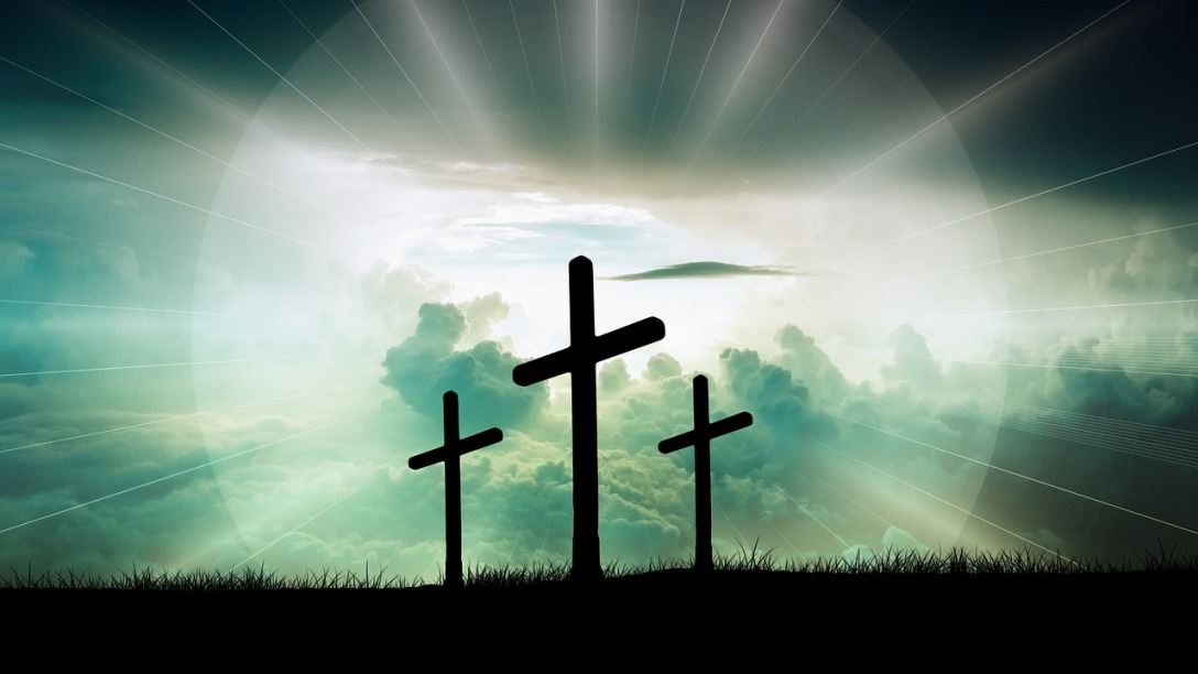 Three crosses are seen the horizon. Behind them light is shining and clouds are visible.