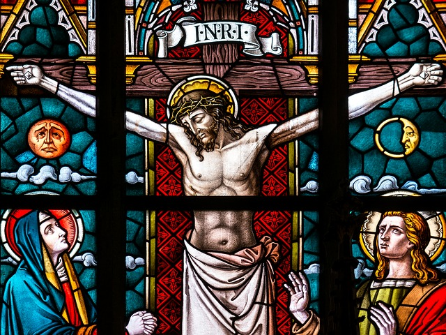 "A stained glass window depicting Jesus' dead body hanging from the cross. ""INRI"" is written above Him. Who appear to be Mary and John can be seen on the left and right side of Him, respectively."