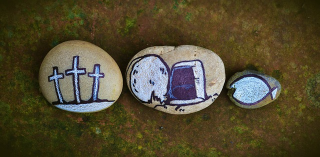 "Three rocks on the ground that are painted on. The first shows three crosses. the second shows an empty tomb. The third is smaller than the other two, and has a ""Jesus fish"" drawn on it."