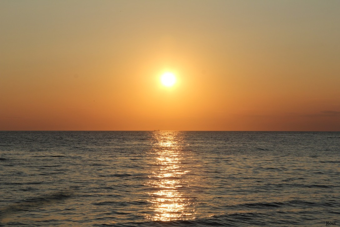 A sun can be seen in the middle of the image. It is setting over the sea. Its reflection is shining on the water.
