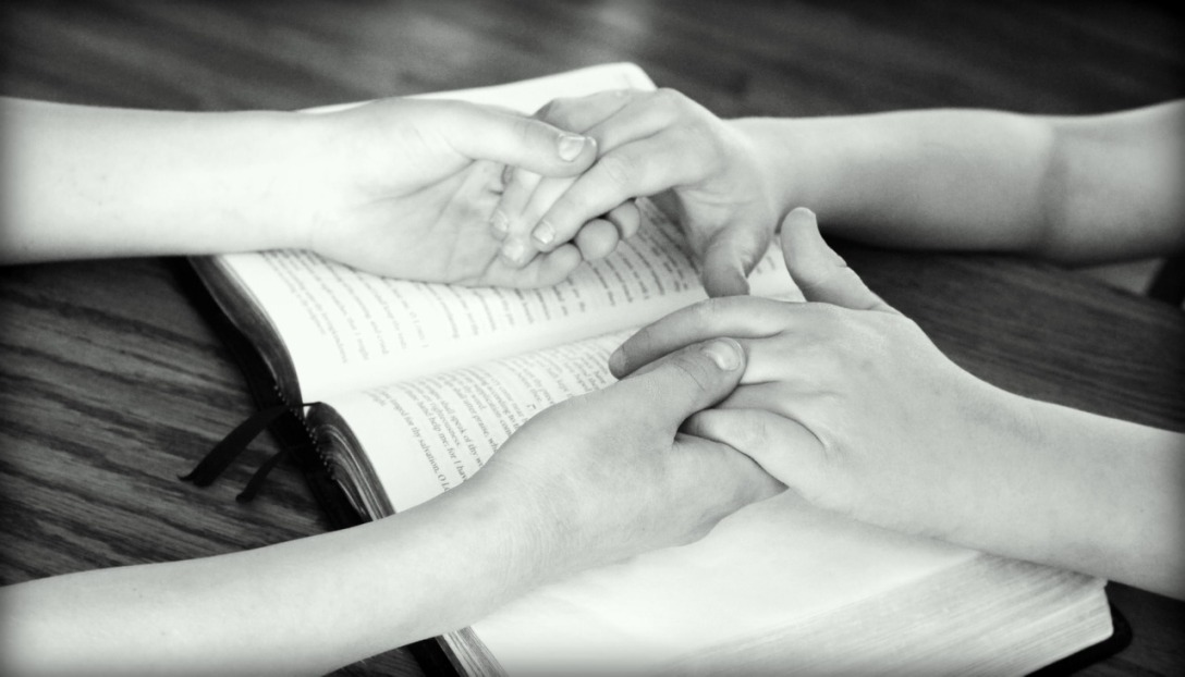 Two people are holding hands over an open Bible. The hands appear to be of two kids, and the Bible is on a wooden table.