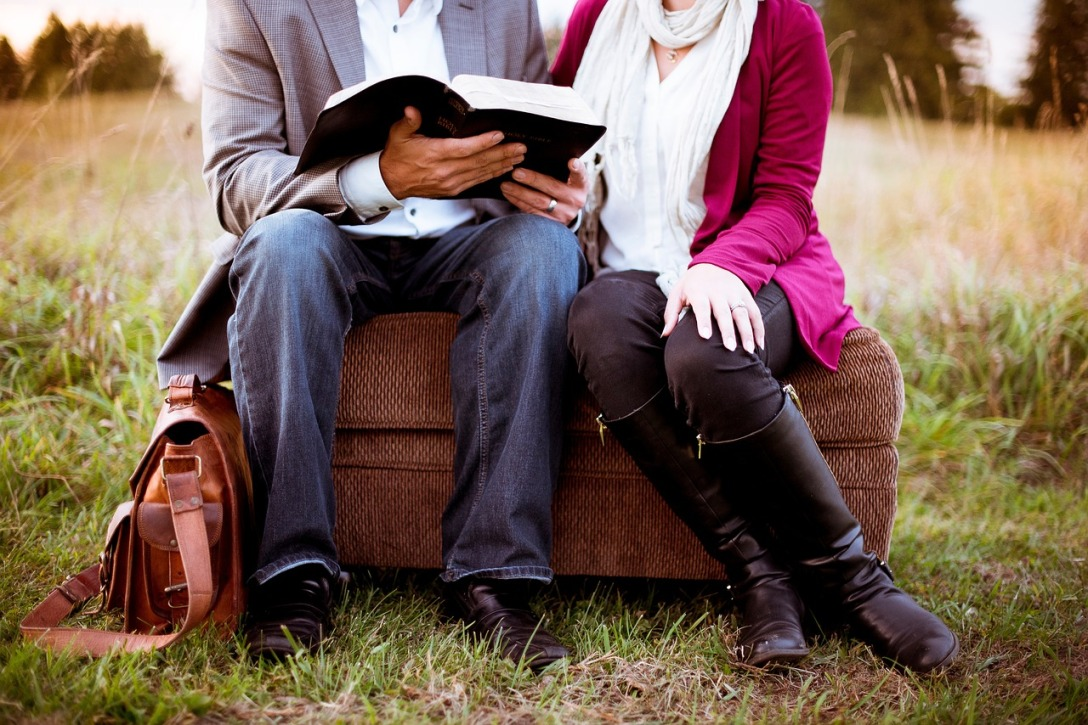 A couple sitting together reading the Bible. They are sitting on an ottoman. Oddly enough, they are sitting on it outside in a field.