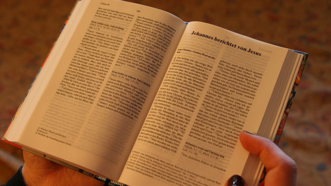 An overhead shot of a woman reading the Bible. It appears to be a German Bible, and she is open to the Gospel of John.