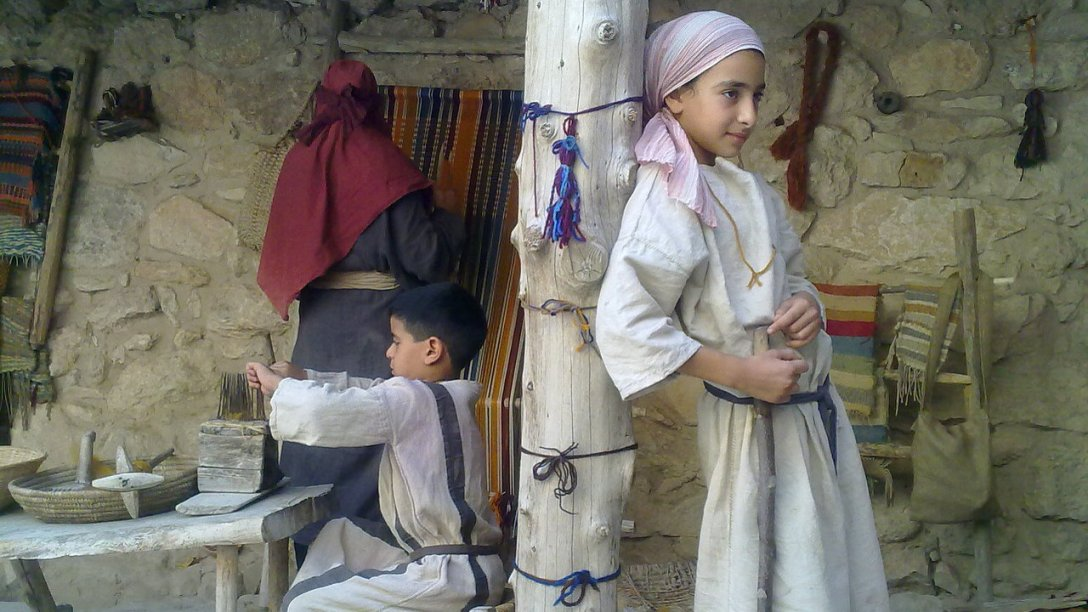 Two young boys in Israel weaving in front of their home. There is a pole in the middle of the image with one of the boys leaning up against it. Another boy on the left is sitting down and working.
