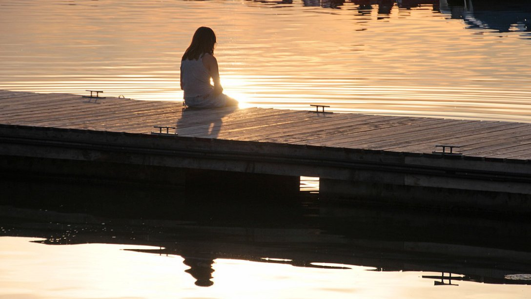 A young girl sitting a dock. A little light is shining off the water, but details of what the girl actually looks like are hard to determine.