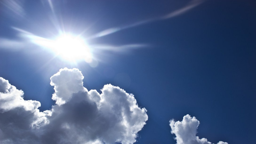 A bright summer sky. A large cloud covers up a large portion of the bottom left of the image. A bright light is visible just above the cloud.