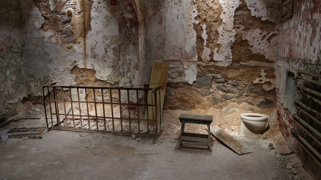 A ruined prison cell. Almost half of the walls don't have paint on them, and the floor is just dirt. There is a bed frame, but it is leaning up against a wall. There is a toilet in the corner, with no way to flush it.