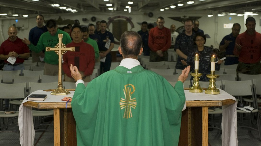 A Catholic Priest standing before a table with his hands to his side and his palms open. From the look of the parishioners, it looks like he is leading the people in prayer.