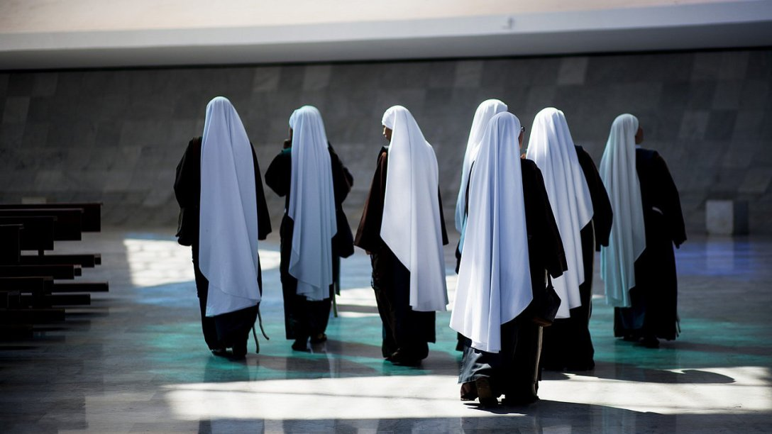 A group of nuns walking together. Their white and black garments are prominent in the image.