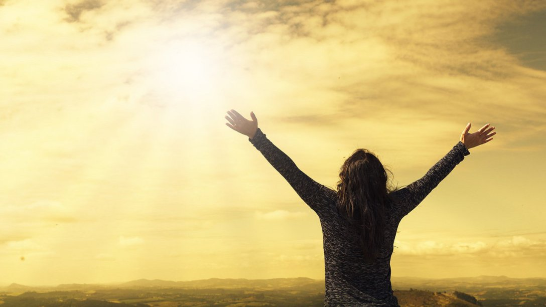A woman looking up at the sun in the sky. Her arms are outstretched in an expression of praise.