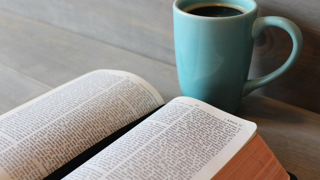 An open Bible with a blue coffee cup on a table.