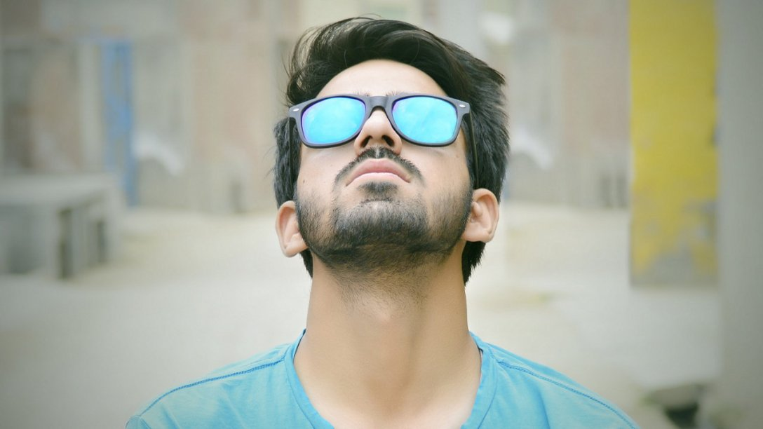 A man looking upward. He has a blue shirt on and his shades have a blue tint to them.