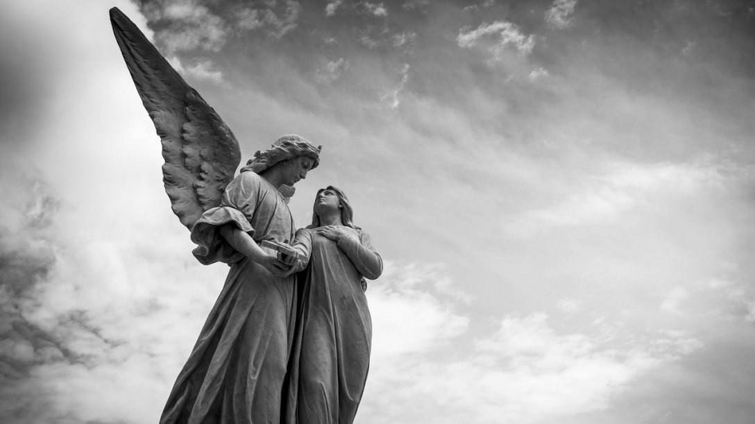 An angel speaking to a person who is nearby. The angel's wing is prominent in the photo, with the angel standing to the side so that it is easier to see. Next to the angel is a person looking up to the angel's face.
