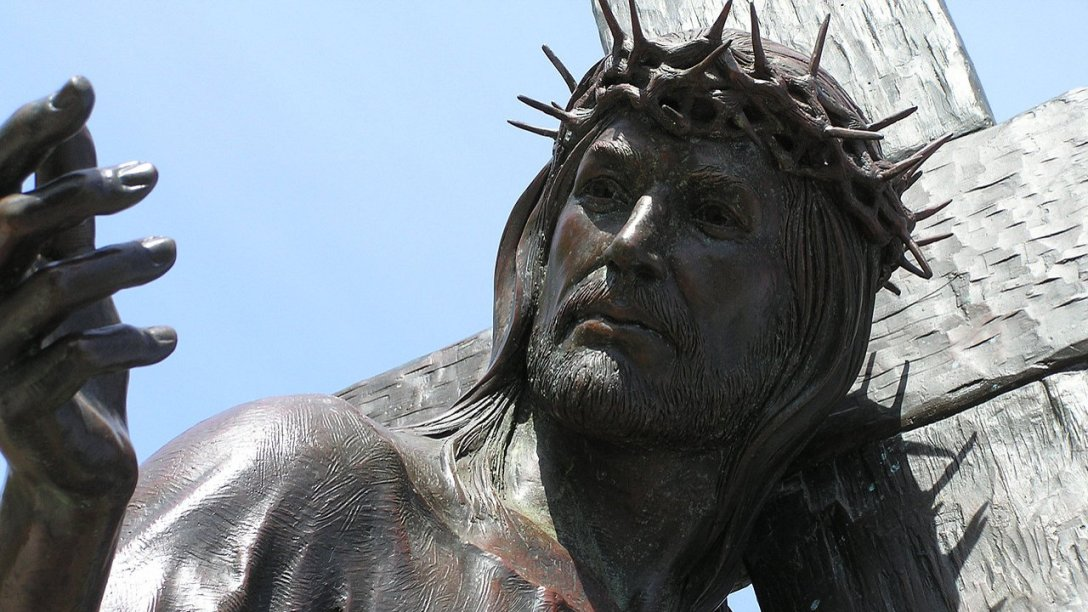 A close-up of a sculpture showing Jesus carrying His cross. In the photo, His cross is over His left shoulder and He is looking toward the right. His right hand is near eye level and on the left side of the image.