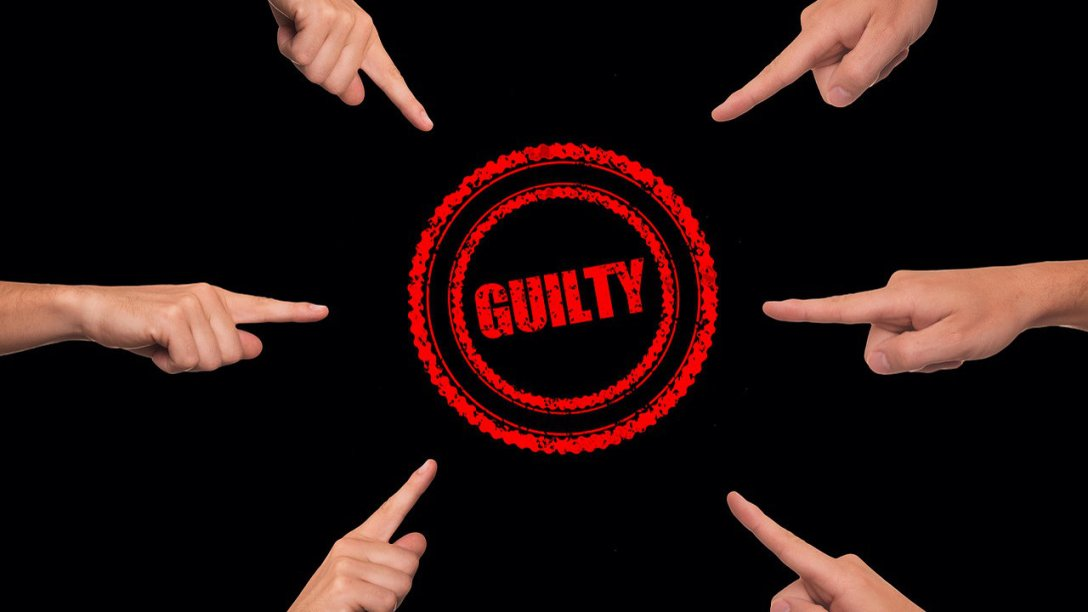 "Hands pointing toward the center of the image, with the word ""Guilty"" in the middle."