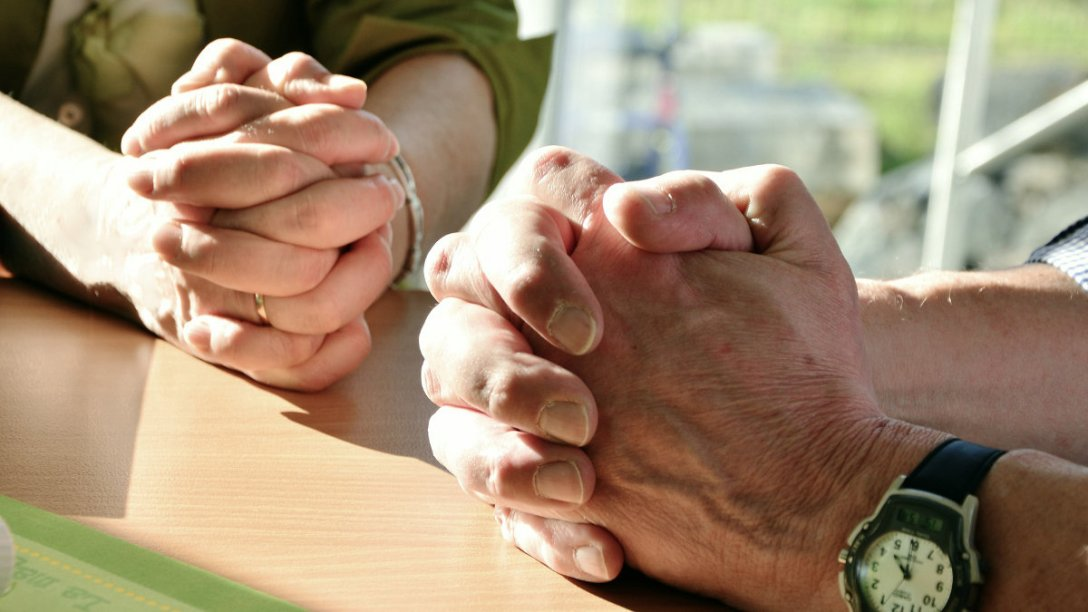 Two people are sitting at a table with their hands together in prayer.