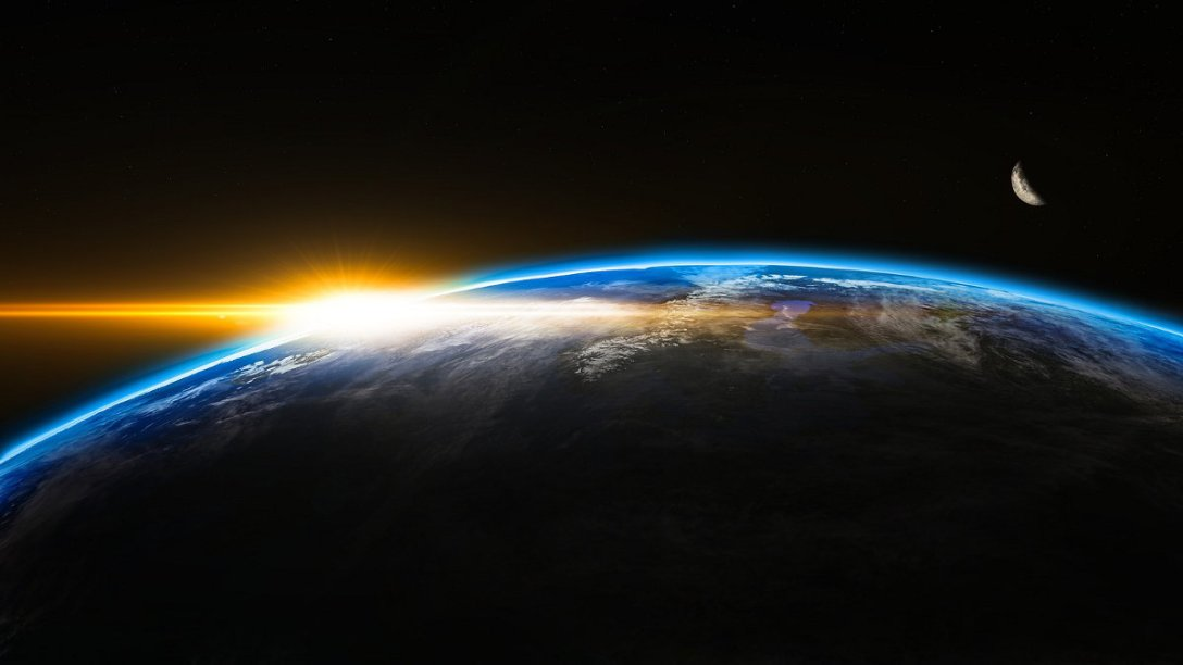 A view of a sunrise over the earth in outer space.