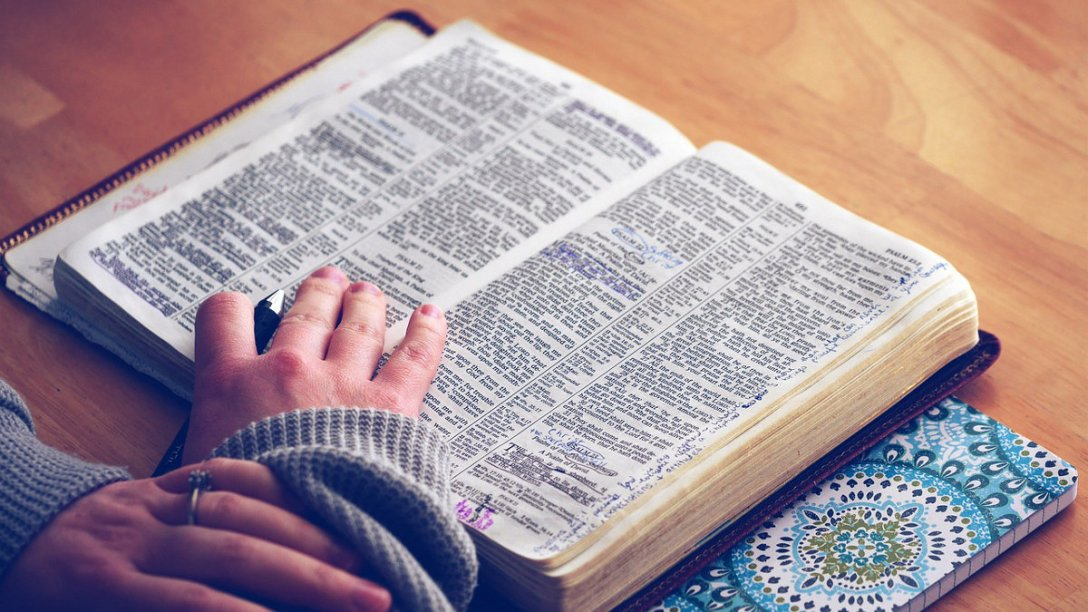 A Bible is open to the book of Psalms. A person has his or her hand on it to keep it open, with a pen tucked between two fingers. He or she is reading, but also ready to make notes in the margins as needed.
