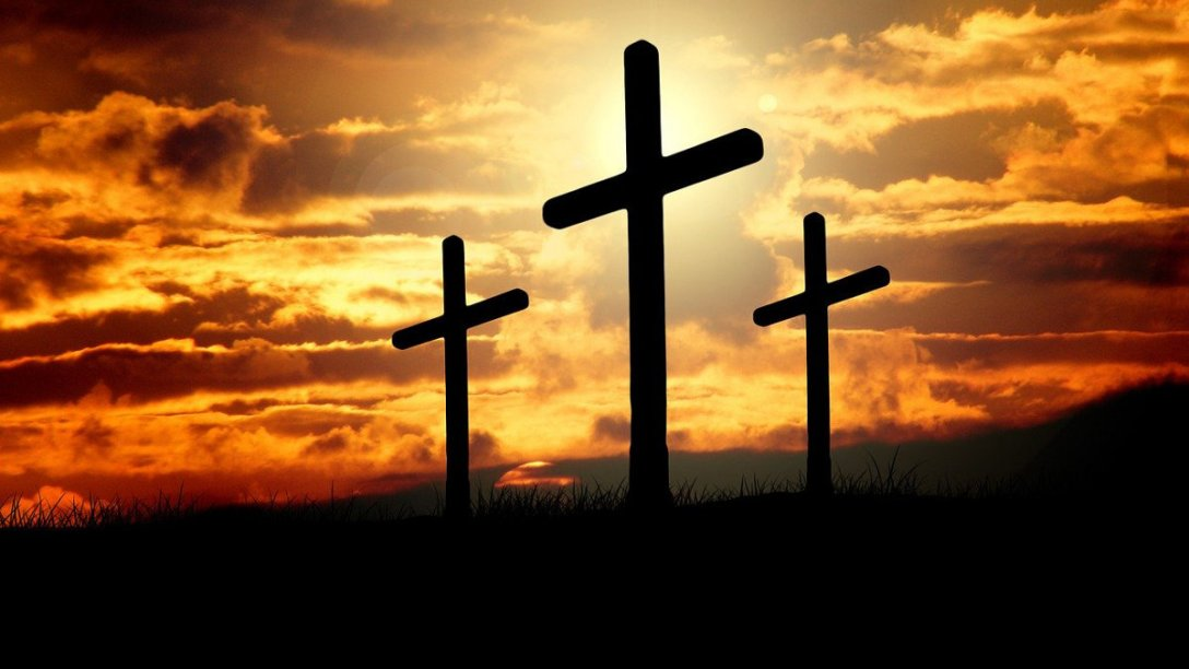 Three crosses on a hill with a sunset behind them.