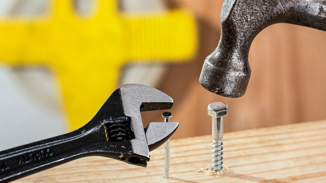 Tools being used in illogical ways. For example, someone is trying to use a wrench to put a nail into a piece of wood.