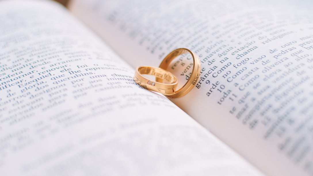 Two wedding rings on an open Bible.