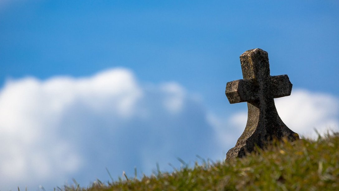 A small cross on a grave with the sky visible in the background.