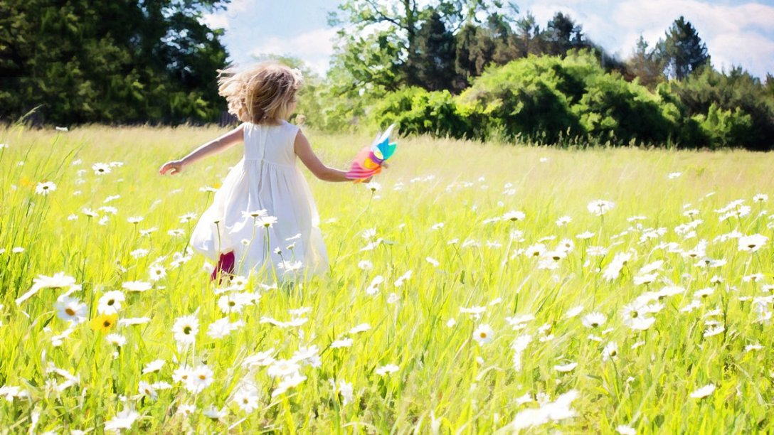 A little girl running through a field of daisies on a bright Summer day.