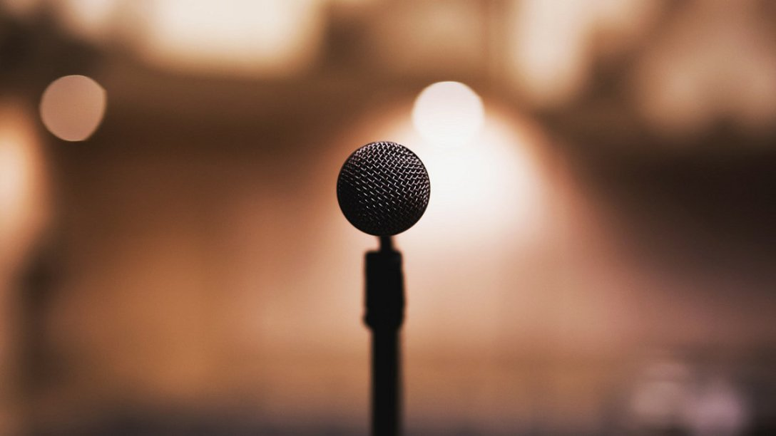 A straight-on shot of a microphone at a concert. Lights can be seen in the background.