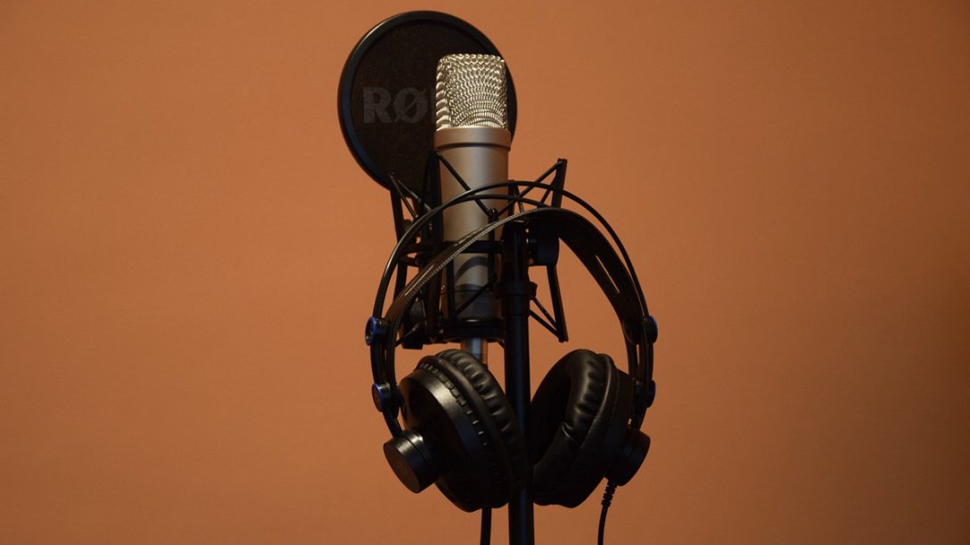 A microphone sitting on its stand, with a pop filter in front of it, and headphones hanging next to it.